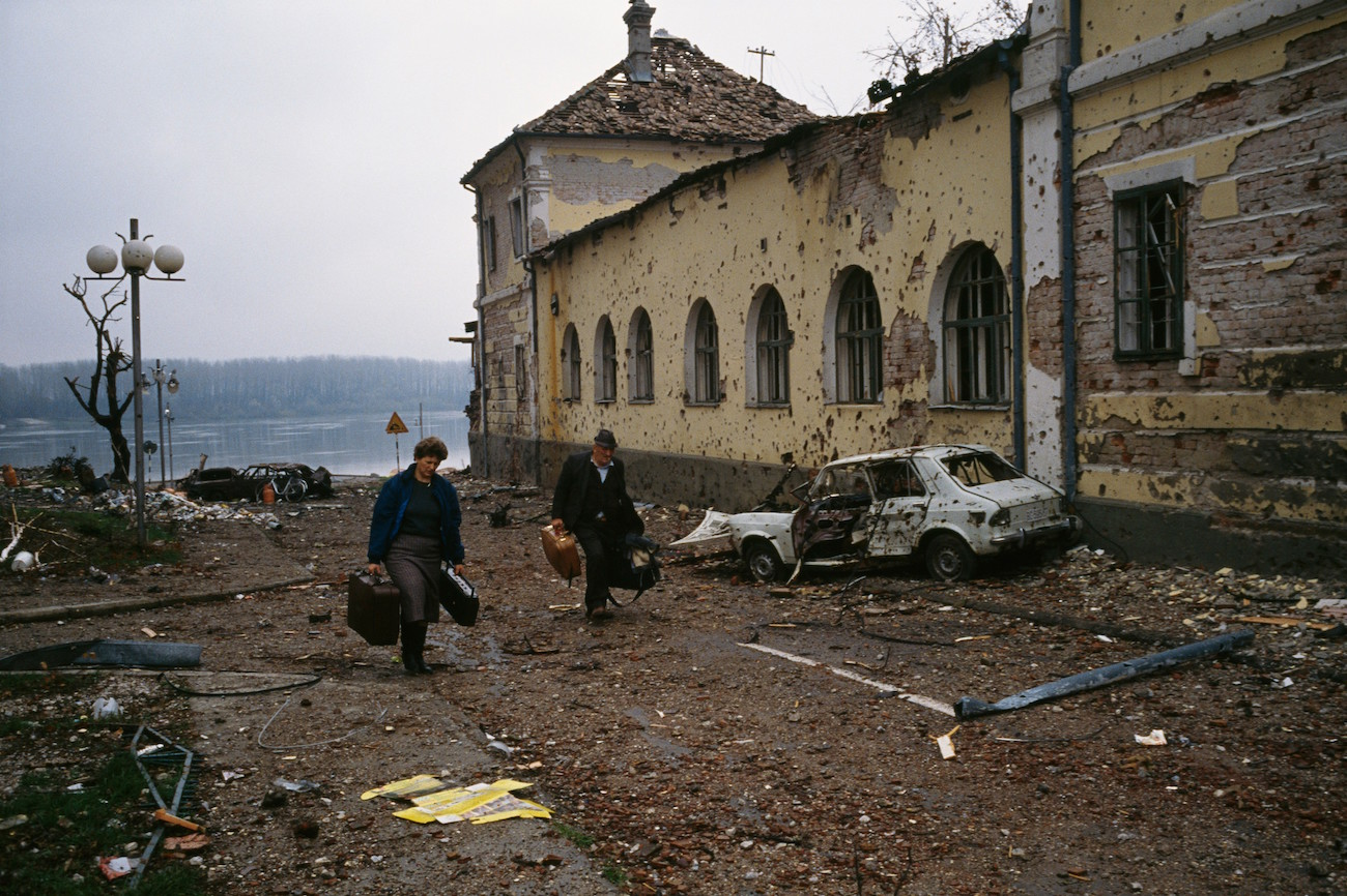 A middle-aged Croatian couple flees the ruined city of Vukovar past bombed buildings riddled with bullet holes and streets filled with rubble after a three-month battle between the Croatian armed forces and the Yugoslavian Federal Army in Vukovar. The Yugoslavian Federal Army completely destroyed the Croatian city and killed thousands of civilians., Image: 16127894, License: Rights-managed, Restrictions: Content available for editorial use, pre-approval required for all other uses. This content may not be materially modified or used in composite content., Model Release: no, Credit line: Profimedia, Corbis